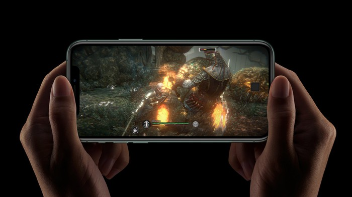 Two hands holding an iPhone 11 Pro that's displaying an image from a mobile game