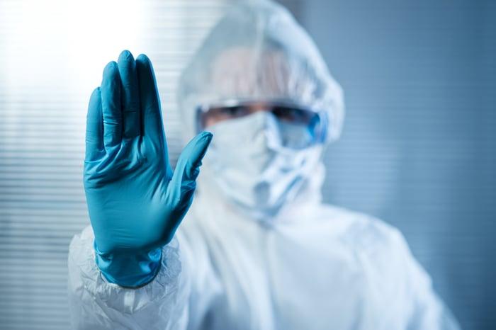 Scientist in hazmat suit raising a gloved hand.