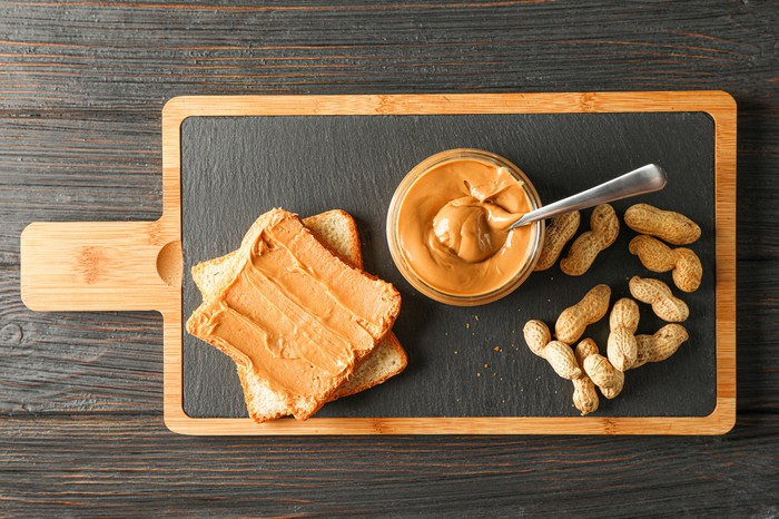 A slice of bread spread with peanut butter is pictured next to a bowl of peanut butter and peanuts on a serving tray.