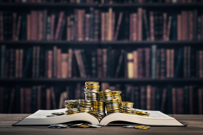 Piles of gold coins on top of a book.