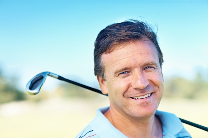 Man smiling with his golf club