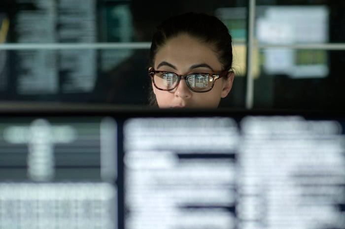 Woman looking at a row of data terminals