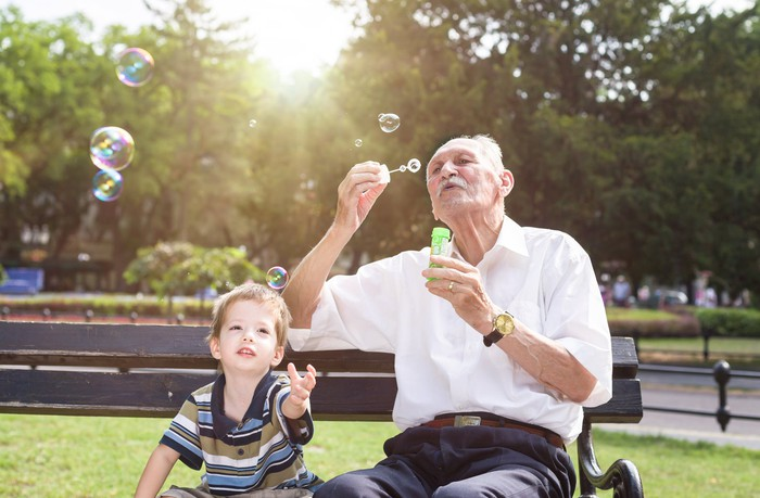 Older man sitting on park bench blowing bubbles while young boy next to him reaches for them