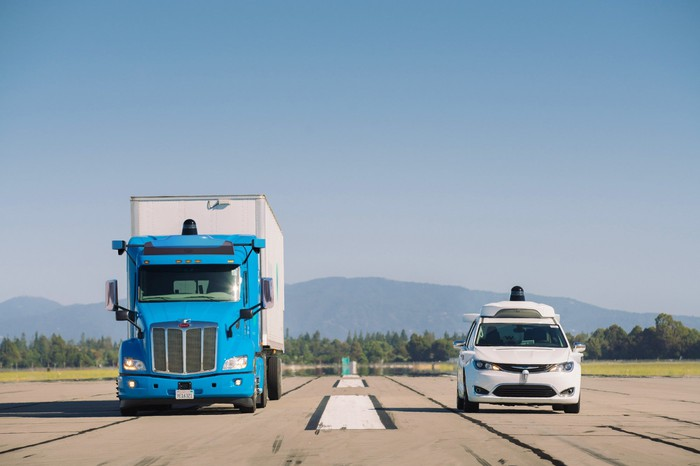 A self-driving truck and self-driving car driving side by side.