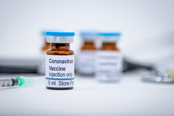 Vials of vaccine solution, labeled 'Coronavirus Vaccine,' sit on a surface.