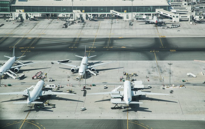 Airplanes parked at a busy airport.