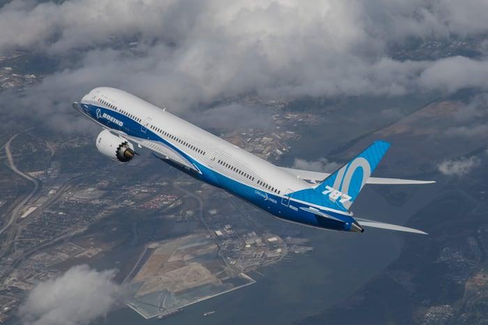 A 787 flies over an industrial setting