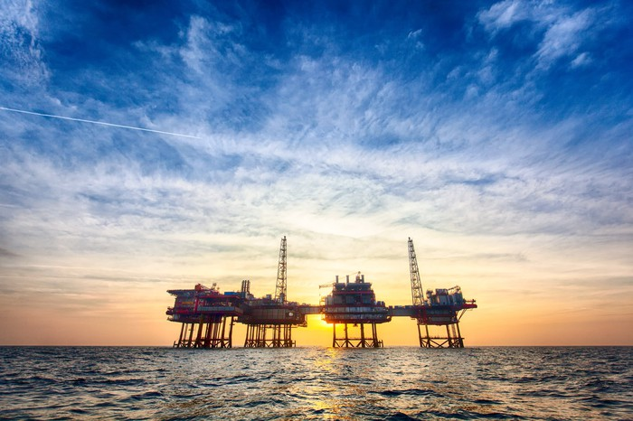 An offshore oil production platform at sunset.
