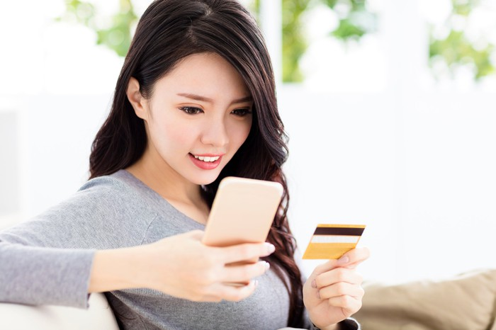 Chinese woman holding credit card and looking at her smartphone