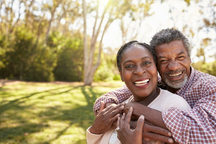 Smiling older man and woman embracing outdoors