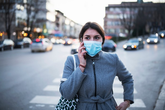 Woman walking across a street, talking on the phone and wearing a face mask.