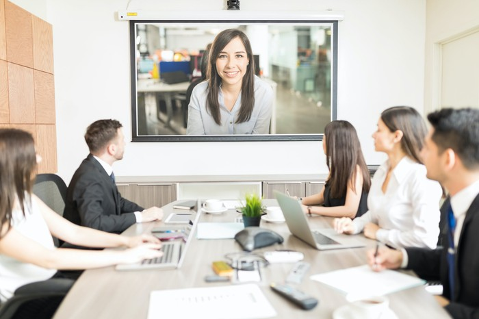 A conference room full of businesspeople videoconferencing with a woman on a TV.