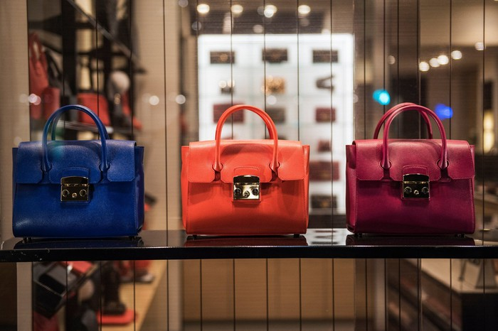 3 leather handbags are shown in a store window.