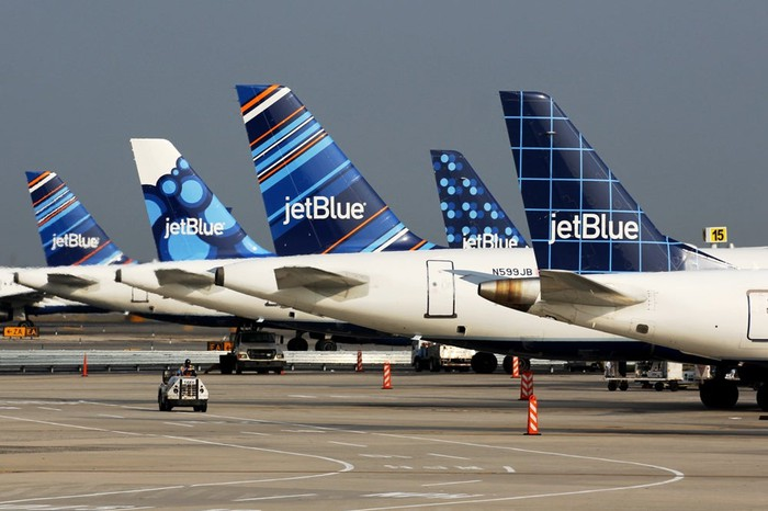 A collection of JetBlue tailfins on display at an airport.