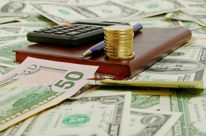 A calculator, book, and pen lying on top of many bills.