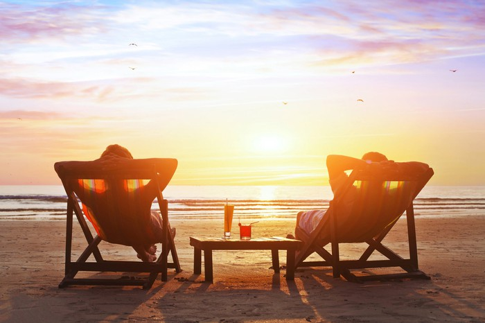 Two people lie on beach chairs with drinks on a table watching the sunset on over the ocean.