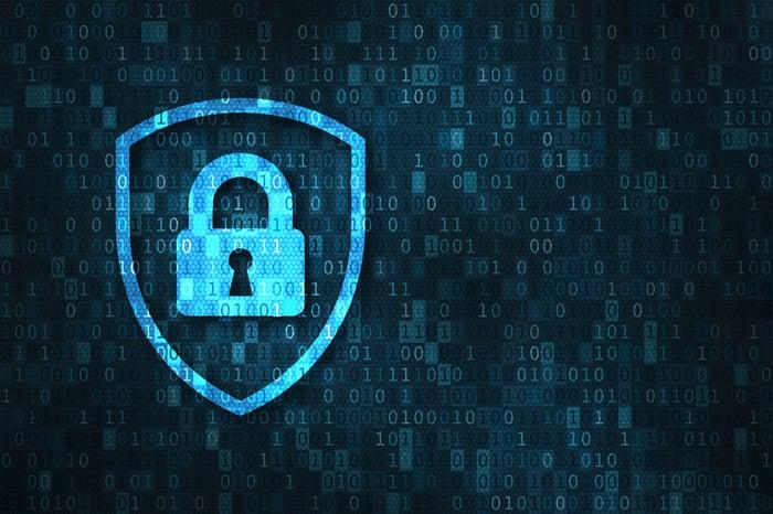 Cybersecurity -- a digital lock in a shield overlaying binary code.
