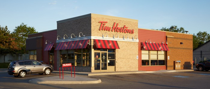 A Tim Horton's restaurant with an SUV parked outside.