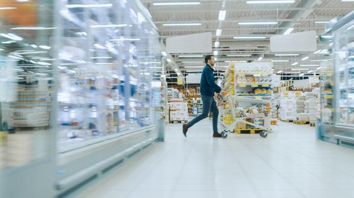 A man pushes a shopping cart through a warehouse store.