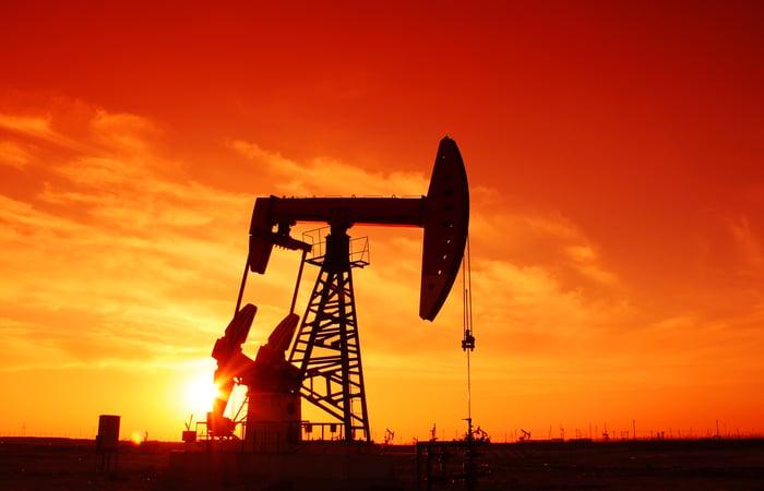 Oil derricks against a sunset