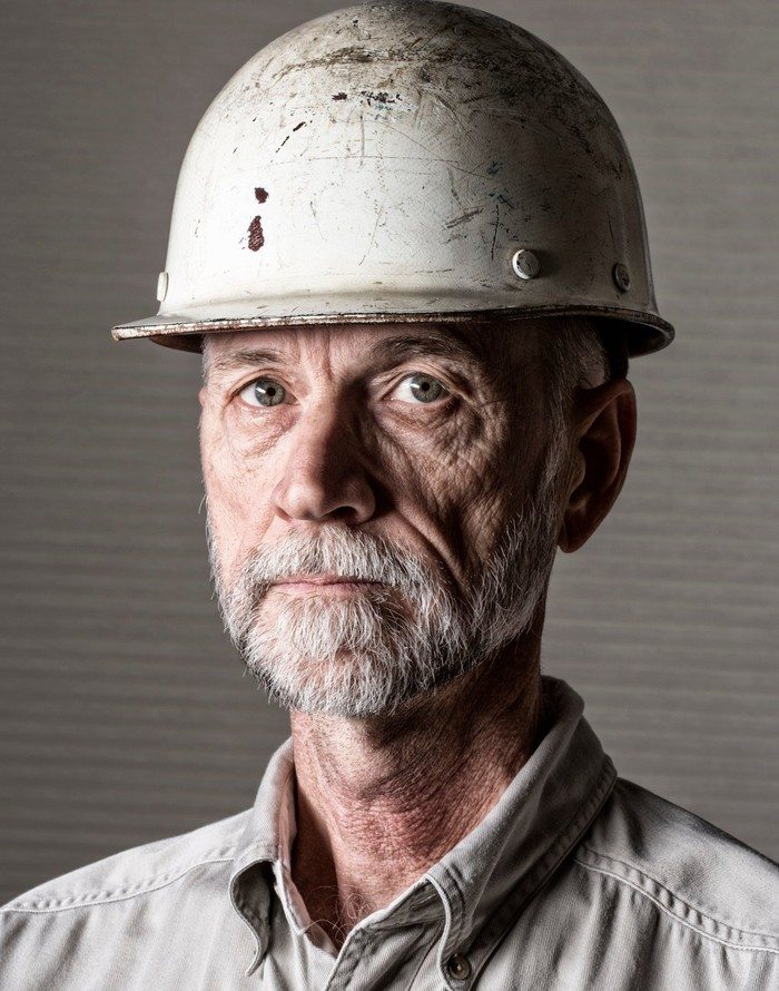Person wearing hard hat and collared shirt.