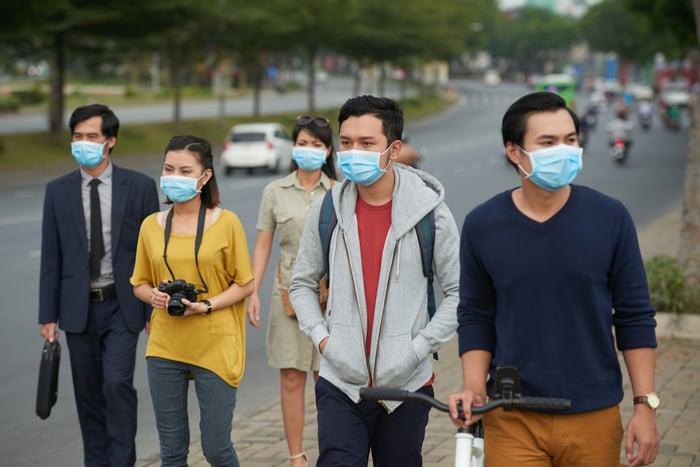 People on the sidewalk wearing masks