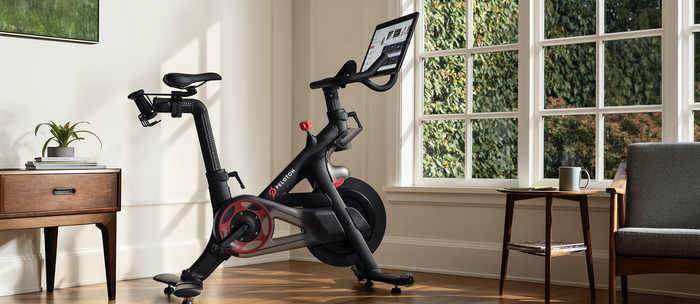 A Peloton exercise bike sitting in a living room.