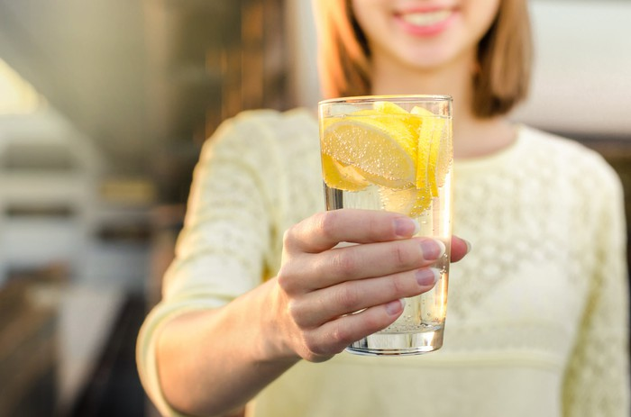 A woman holding a glass of sparkling water with lemon.
