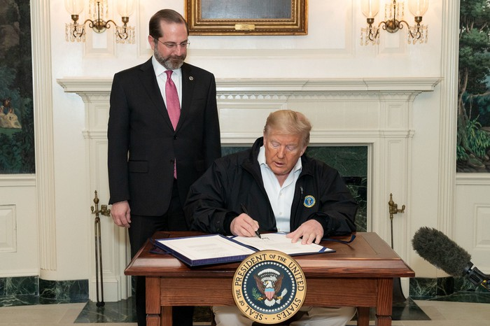 President Tump, flanked by Secretary of Health and Human Services, signs the coronavirus bill into law.