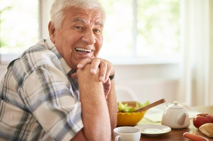 Smiling older man resting chin on hands
