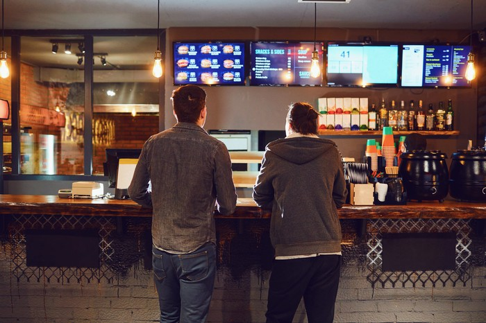 Two Men standing at the counter of a fast-food reastaurant