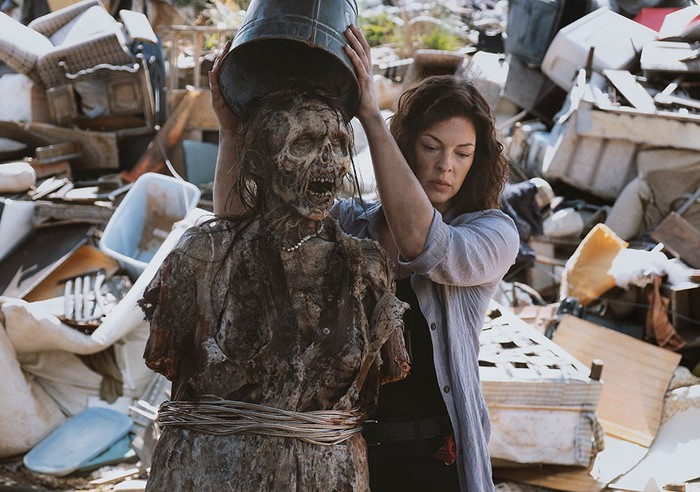 A woman puts a bucket over the head of a zombie in a Walking Dead scene.