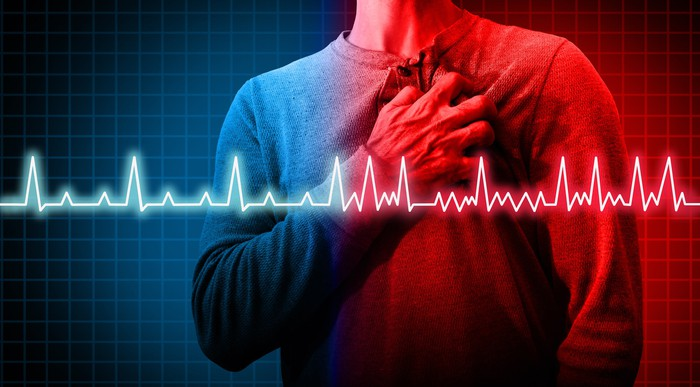Man holding chest with heart rate graph superimposed.