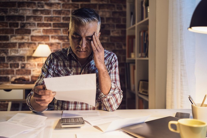 Older man holding his head while reading document, sporting worried expression