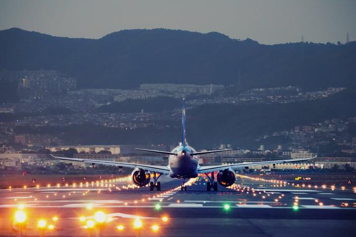A plane landing on an airstrip.