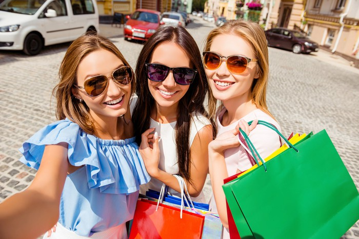 Three smiling women with shopping bags