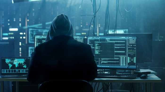 A hooded hacker in a darkened room full of computers, monitors, and cables.