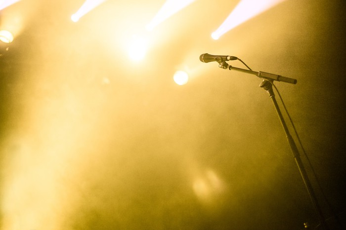 A microphone on a mic stand, surrounded by stage smoke and dramatic yellow lighting. There is no singer.