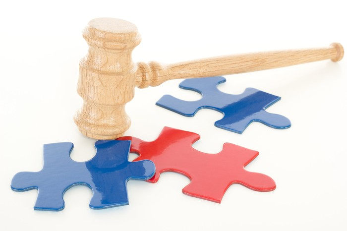 A wooden gavel hitting a handful of puzzle pieces that aren't fitting together.