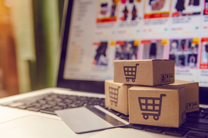 small cardboard boxes with a shopping cart icon printed on them lie next to a laptop and credit card suggesting e-commerce.