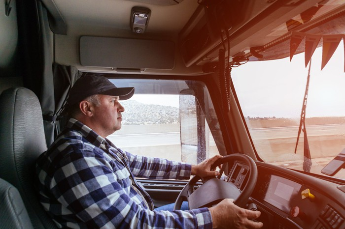 Truck driver behind the wheel, in truck cab