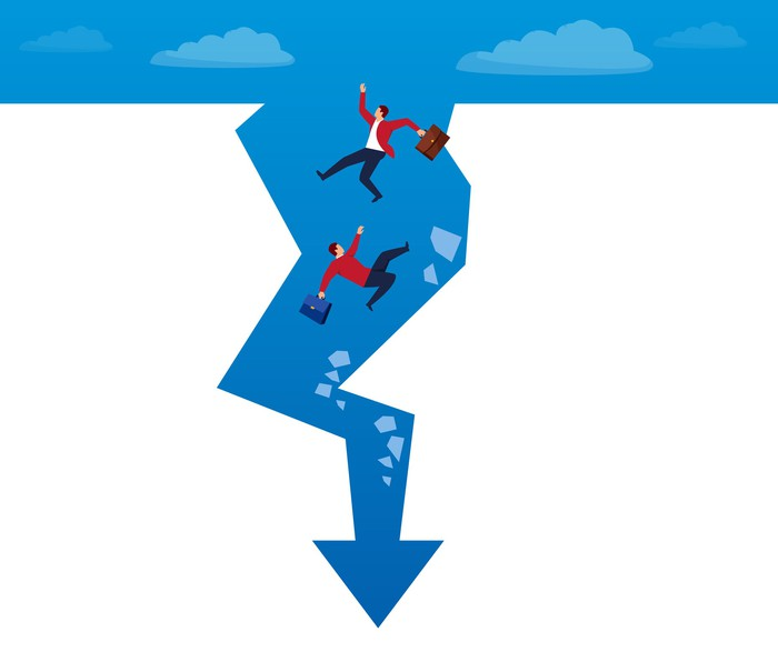 businessmen falling off a cliff