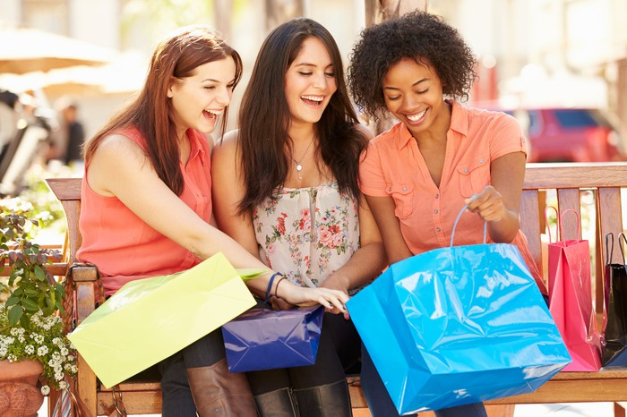 Three young women seated on an outdoor bench while happily looking inside a blue shopping bag.