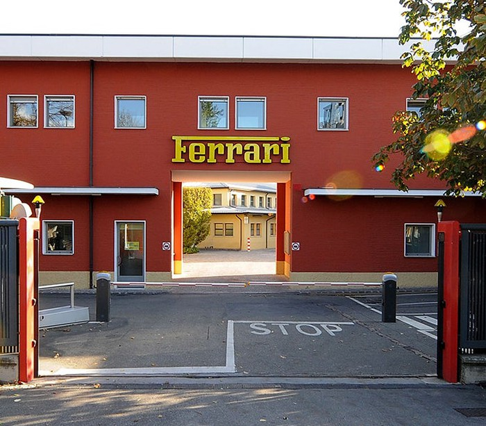 A red building with the Ferrari name, the landmark entrance to Ferrari's factory complex.