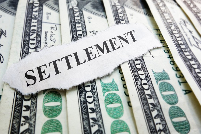 The word settlement typed on a piece of paper lying on top of hundred-dollar bills