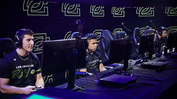 Esports players sitting in front of computers and wearing headsets.
