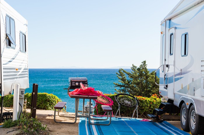A beach is seen between two parked RVs.