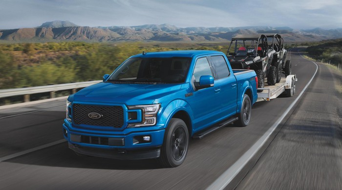 A blue 2020 Ford F-150, a full-size pickup truck, is shown pulling a trailer.