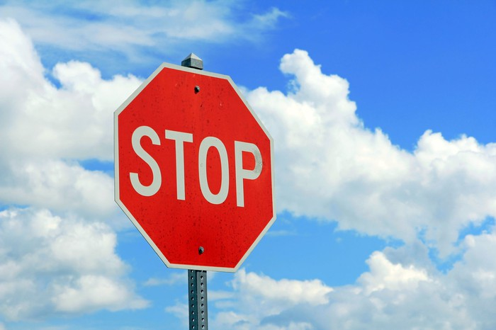 Red stop sign against a blue sky with clouds.