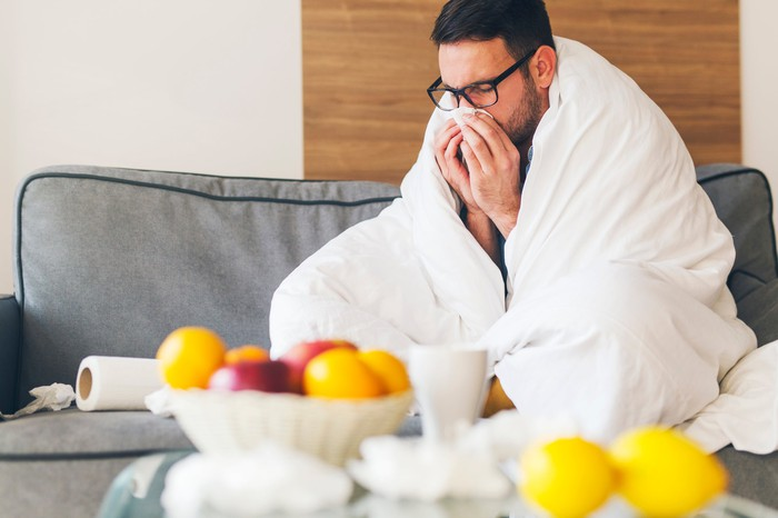 A man wrapped in a blanket sneezing into a tissue while sitting on a couch.